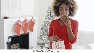 Astonished young woman holding a Christmas gift bag in her...