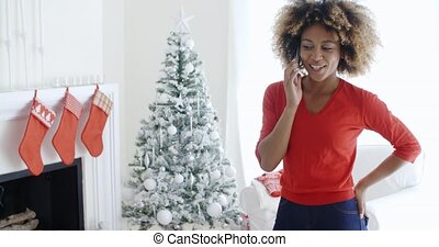 Happy young woman chatting on her mobile at Xmas