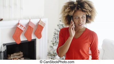 Trendy young woman chatting on her mobile at Xmas
