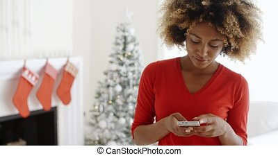Young woman checking her Christmas messages - Attractive...