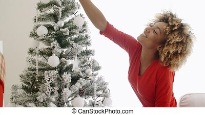 Attractive African woman decorating the Xmas tree -...