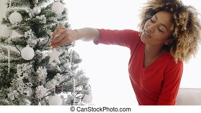 Pretty young African woman decorating an Xmas tree - Pretty...