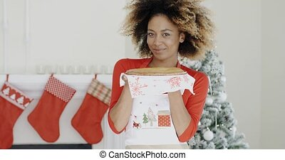 Happy young woman holding a Christmas pastry