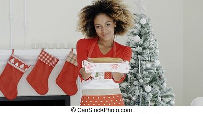 Happy trendy young woman with a Christmas dessert or pastry...