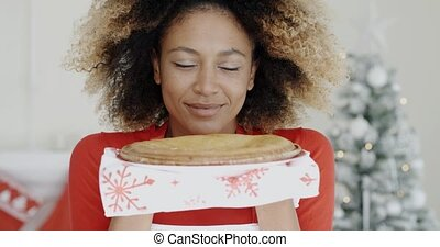 Young woman with a fresh Christmas tart - Young African...