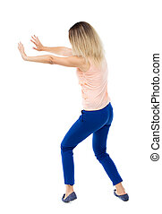 back view of woman pushes wall Isolated over white...