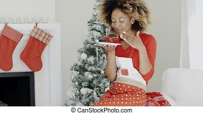 Happy young African woman celebrating Christmas looking with...