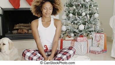Cute young woman and her dog at Christmas sitting together...