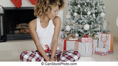 Young woman enjoying Christmas sitting cross-legged on the...