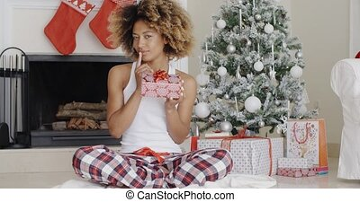 Pretty smiling woman displaying a Christmas gift - Pretty...