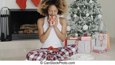 Blissful young woman drinking coffee at Christmas - Blissful...