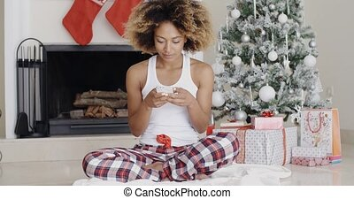 Young woman sending a Christmas message - Young woman...