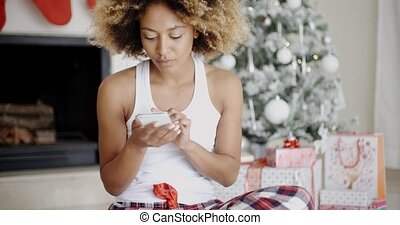 Serious woman checking for Christmas messages - Serious...
