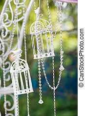 Decorative glass cages hanging on chains. Wedding decor.