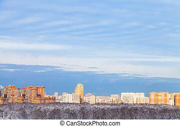 blue sky over city illuminated by evening sun