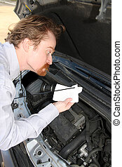 checking engine oil dipstick - Funny man checking engine oil...