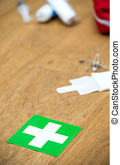 First aid kit and green cross on a wooden surface