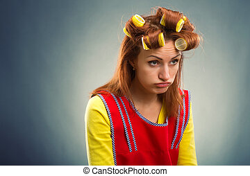 Sad housewife with curlers on her hair - Unhappy housewife...
