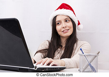 girl with christmas hat and computer