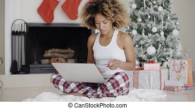 Young woman shopping online for Christmas sitting on the...
