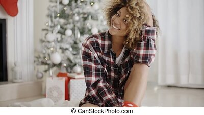 Thoughtful woman in front of a decorated Xmas tree -...