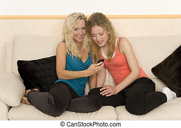 spare time - two young girls having fun with an mobile phone