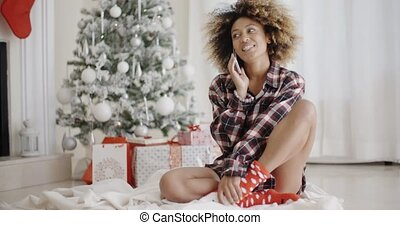 Young woman relaxing in front of a Christmas tree - Young...