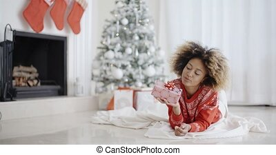 Young African girl lying looking at her Xmas gift - Young...