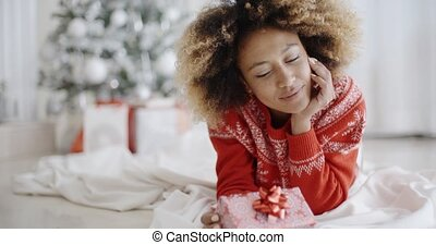 Thoughtful young woman with a Christmas gift - Thoughtful...