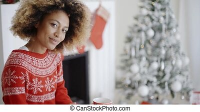 Smiling woman drinking a mug of Christmas coffee