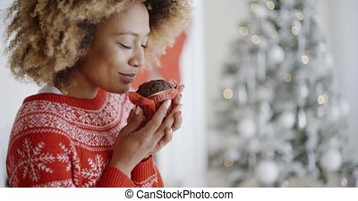 Young woman savoring a Christmas cake - Young African woman...