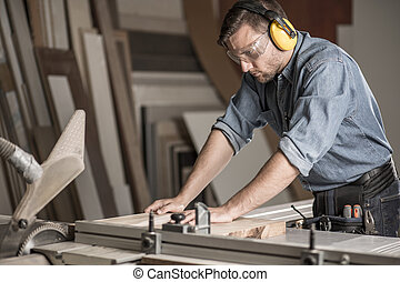 Carpenter cutting wood on workbench - Image of young...