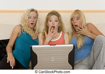 spare time - a group of young teenager looking on the laptop...
