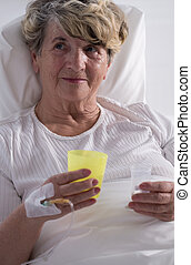 Hospice patient taking painkillers - Photo of senior hospice...