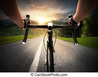 Ride in the sunshine - Cyclist pedaling on a street in...