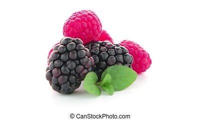 Raspberries and blackberry with mint leaf isolated on white...