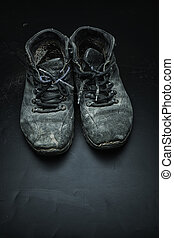Old worn out shoes - Old black worn out shoes on the black...