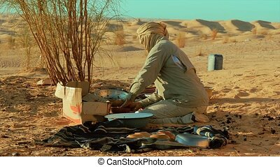 a sahara man washing dishes - a man camping in the sahara...
