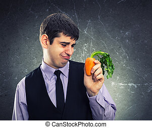 Small carrot in hand of a dissapointed man
