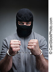 Thief in black mask - Criminal in black mask with handcuffs...