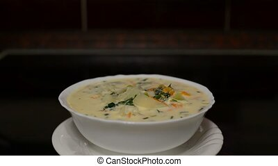 Plate with cheese soup is on  stove