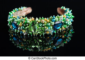 diadem with large green stones. bijouterie. on black background