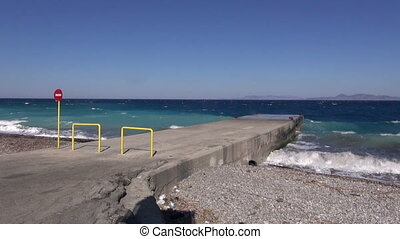 Waves rolling on a pier on beach - Breakwater made of cement...