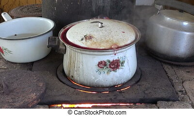 Pot boiling on hearth in rural area