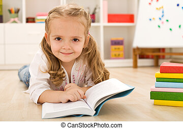 Happy little girl practicing reading laying on the floor in...