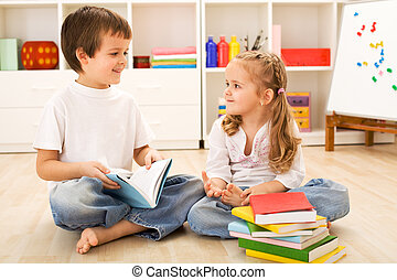 School boy showing her little sister how to read - Happy...