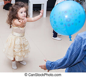 Kids playing balloon at home - Curly-haired baby girl...