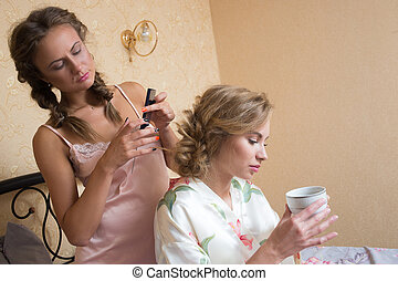 Girl doing hairstyle girlfriend in bed. bedroom. young...