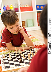 Serious chess player kid thinking about the next move laying...