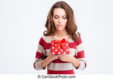 Portrait of a pensive woman holding gift box isolated on a...